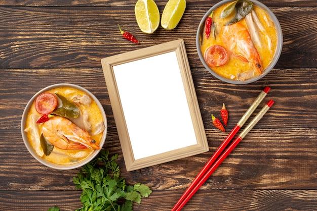 Soupes à angle élevé dans des bols avec citron aux crevettes et baguettes avec cadre vide