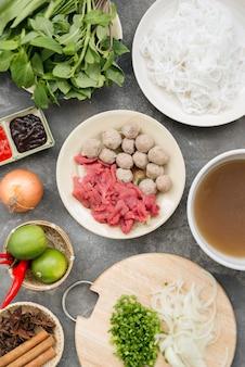 Soupes de nouilles vietnamiennes traditionnelles pho dans des bols, fond de béton. soupe de boeuf vietnamienne pho bo, gros plan. cuisine asiatique/vietnamienne. dîner vietnamien. repas pho bo. vue de dessus. sain