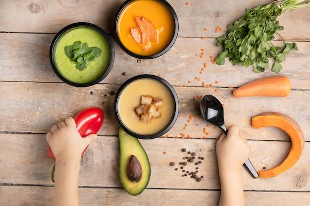 Soupes de régime végétalien pour la santé, repas prêt à manger dans les boîtes à lunch et les enfants à la cuillère