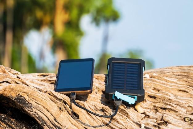 Source d'énergie alternative. la batterie est chargée par l'énergie solaire. charger des appareils mobiles dans la nature. plage de l'île. powerbank charge le téléphone sur fond de palmiers et de plage de sable