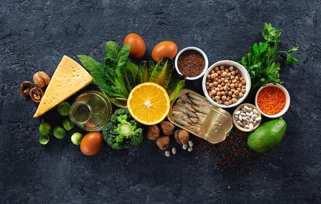 Sources alimentaires d'oméga 3 et de graisses saines sur une vue de dessus sombre.
