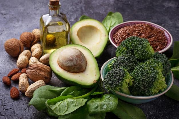 Sources végétales grasses - lin, épinards, brocoli, noix, olives, huile et avocat. concept de foo en bonne santé