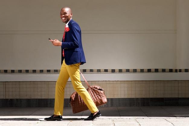 Souriant africain homme d'affaires marchant avec sac et téléphone