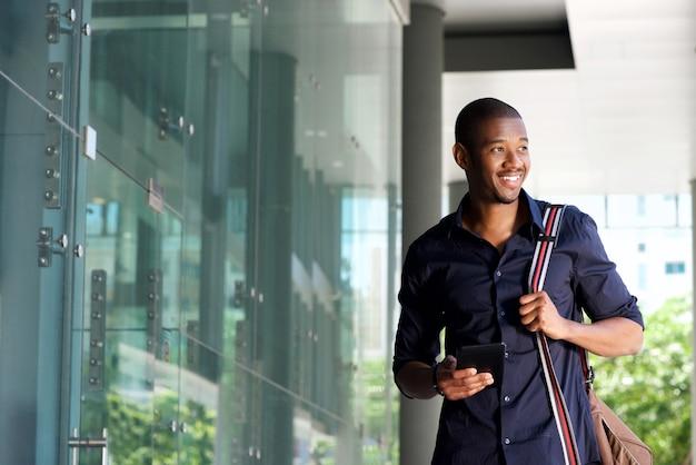 Souriant africain homme marchant avec téléphone portable et sac