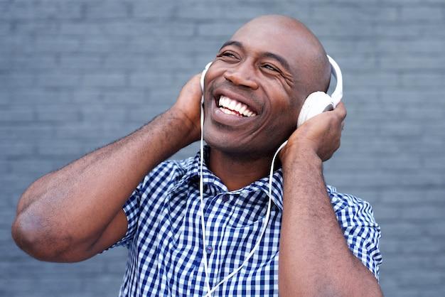 Souriant afro-américain écoute de la musique avec des écouteurs