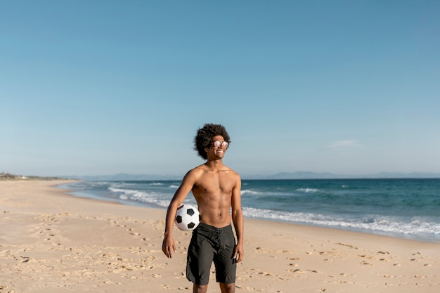 Souriant afro-américain mâle debout avec ballon au bord de mer
