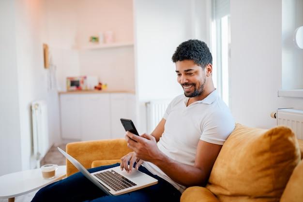 Souriant afro-américain travaillant à la maison tout en étant assis sur le canapé. utiliser un téléphone portable et un ordinateur portable.
