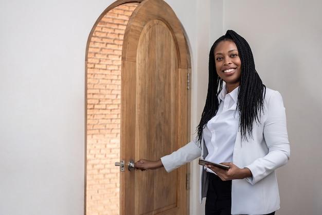 Souriant agent immobilier femme afro-américaine à l'intérieur de la maison