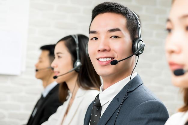 Souriant, agent de télémarketing du service clientèle asiatique en centre d'appels