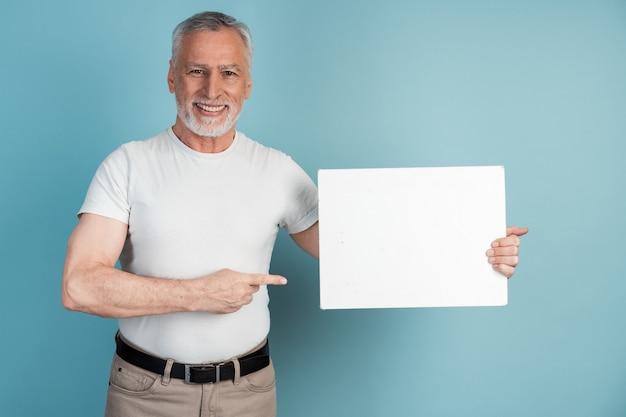 Souriant, agréable, homme âgé tient un morceau de papier blanc et le montre du doigt.