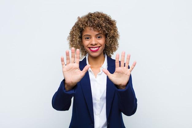 Souriant et à l'air amical, montrant le numéro dix ou dixième avec la main en avant, compte à rebours
