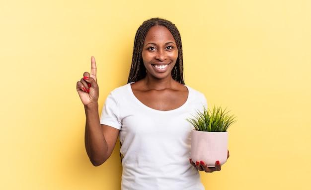 Souriant et l'air amical, montrant le numéro un ou le premier avec la main en avant, comptant à rebours tenant un pot de plante
