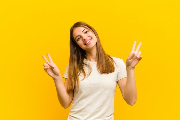Souriant et l'air heureux, amical et satisfait, gesticulant victoire ou paix à deux mains