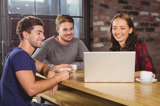 Souriant amis ayant café ensemble et regardant un ordinateur portable