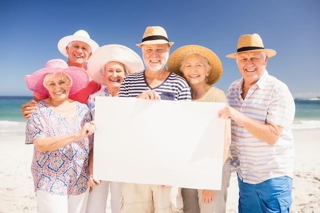 Souriant amis seniors tenant une pancarte vierge