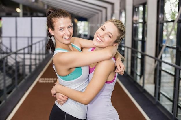Souriant amis sportifs embrassant sur piste