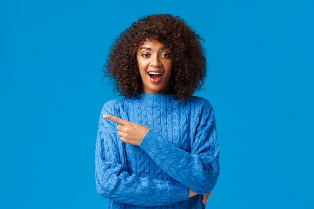 Souriant amusé, heureux et fasciné femme afro-américaine profitant des vacances d'hiver