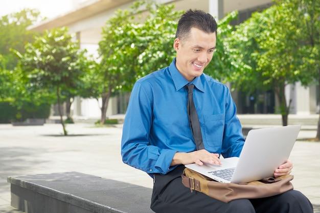 Souriant asiatique homme d'affaires à l'aide d'un ordinateur portable
