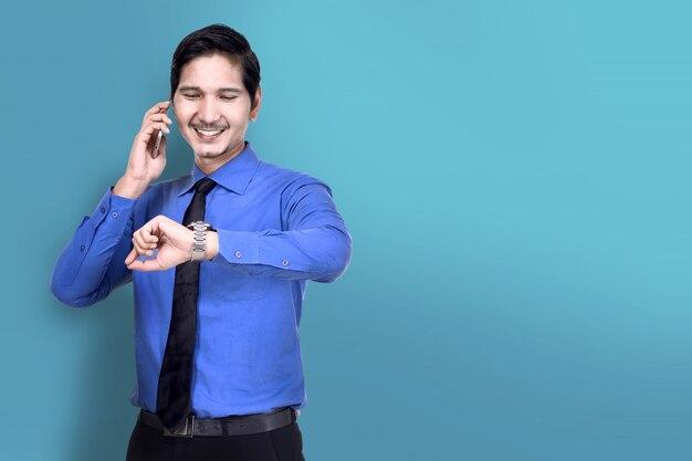 Souriant asiatique homme d'affaires vérifier la montre tout en parlant au téléphone