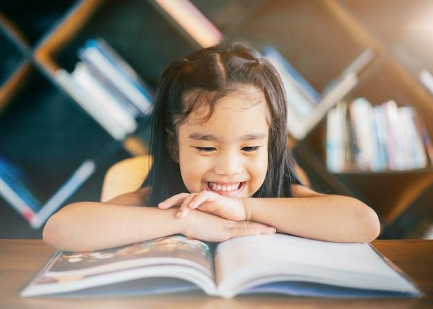 Souriant asiatique petite fille lisant un livre dans le salon à la maison.