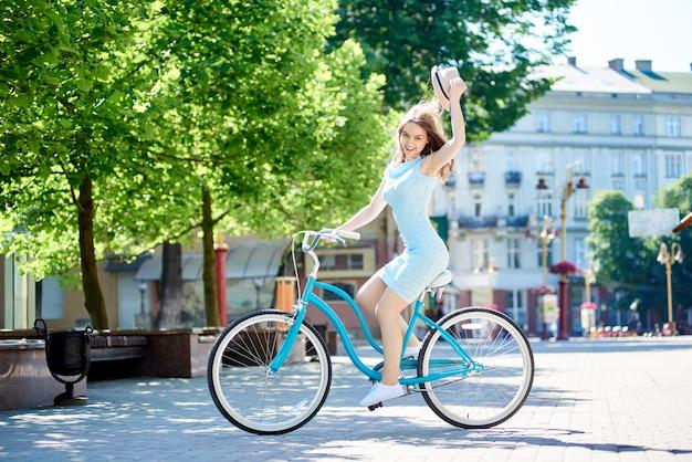 Souriant attrayant femme tenant un chapeau alors qu'il faisait du vélo bleu dans le centre-ville pavée