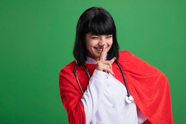 Souriant aux yeux fermés jeune fille de super-héros portant un stéthoscope avec une robe médicale et une cape montrant le geste de silence isolé sur le mur vert