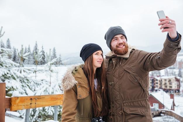 Souriant beau jeune couple debout et prenant selfie avec téléphone portable à l'extérieur en hiver