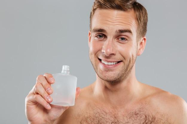 Souriant beau jeune homme appliquant une lotion après rasage sur le visage sur un mur gris