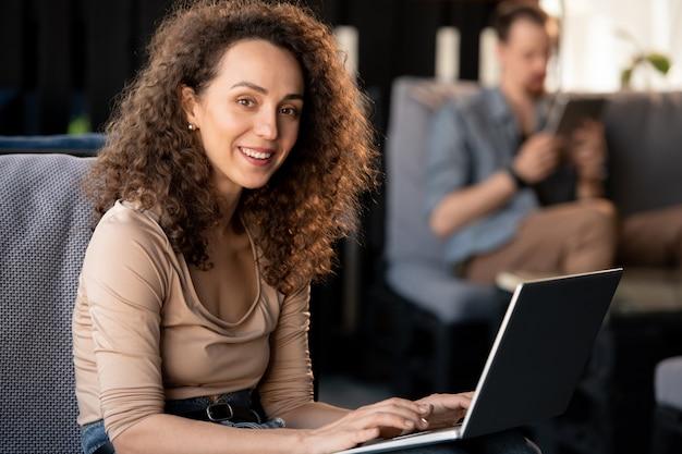 Souriant beau jeune homme barbu en chemise en jean tapant sur un ordinateur portable moderne tout en travaillant dans un café