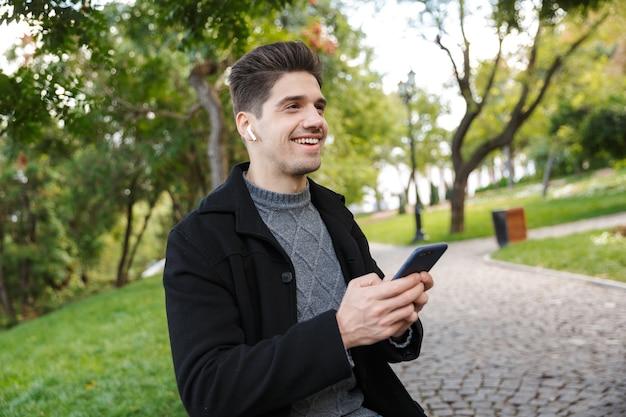 Souriant beau jeune homme gai dans des vêtements décontractés marchant à l'extérieur dans un parc verdoyant à l'aide de téléphone portable écoutant de la musique avec des écouteurs.