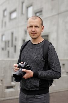 Souriant beau photographe masculin avec appareil photo reflex numérique moderne posant sur fond de bâtiment en béton
