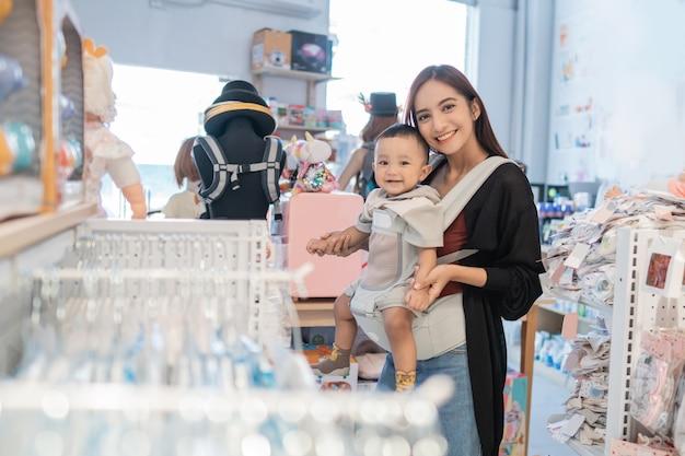 Souriant bébé heureux avec sa mère dans le centre commercial