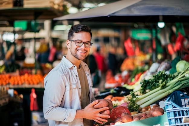 Souriant bel homme achète des légumes au marché de rue.