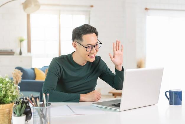 Souriant bel homme d'affaires asiatique travaillant à distance depuis chez lui. il est en vidéoconférence webinaire.