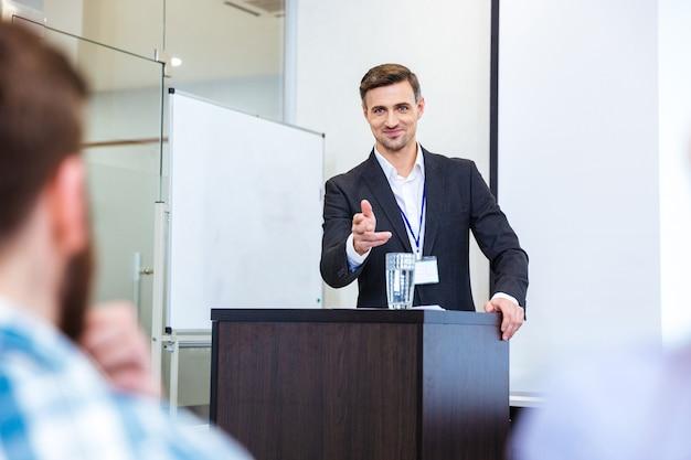 Souriant bel homme d'affaires debout à la tribune dans la salle de conférence et pointant dans l'auditoire