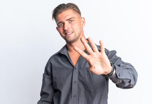 Souriant bel homme blond gesticulant quatre avec les doigts