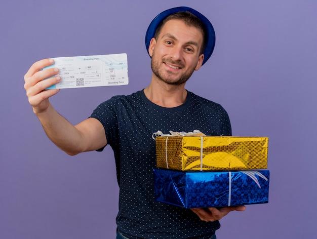 Souriant bel homme caucasien portant un chapeau bleu détient des coffrets cadeaux et un billet d'avion isolé sur fond violet avec espace copie