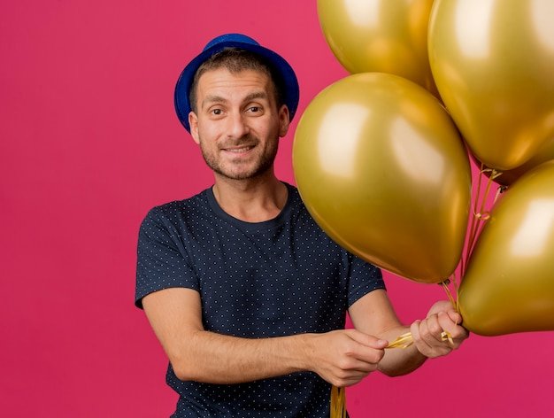 Souriant bel homme caucasien portant chapeau de fête bleu détient des ballons d'hélium isolés sur fond rose avec espace de copie