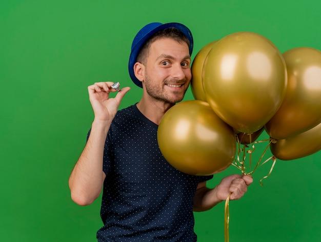 Souriant bel homme caucasien portant chapeau de fête bleu détient des ballons d'hélium et sifflet de fête isolé sur fond vert avec espace copie