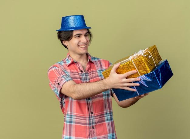Souriant bel homme caucasien portant un chapeau de fête bleu tient et regarde les coffrets cadeaux