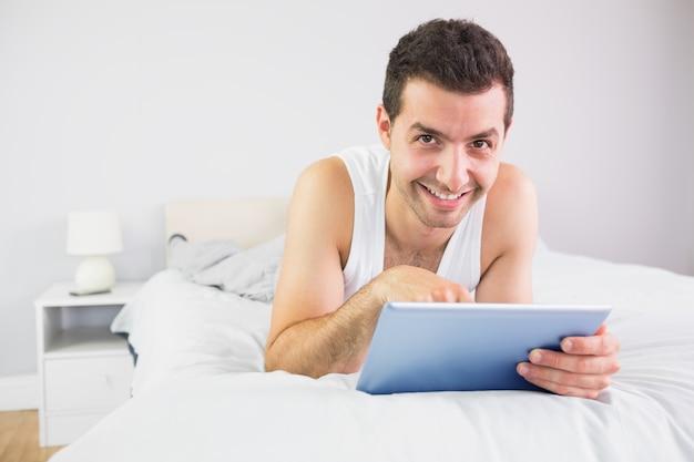 Souriant bel homme couché dans son lit avec tablette