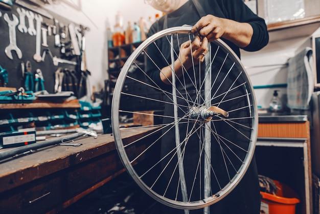 Souriant bel homme de race blanche tenant la roue de bicyclette dans les mains en se tenant debout dans l'atelier.