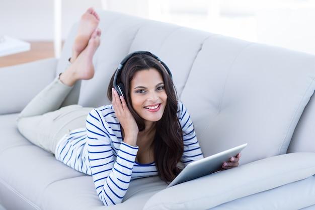 Souriant belle brune écoute de la musique tout en utilisant sa tablette