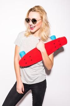 Souriant belle fille de patineur blodnie en lunettes de soleil brillantes reste devant le mur blanc