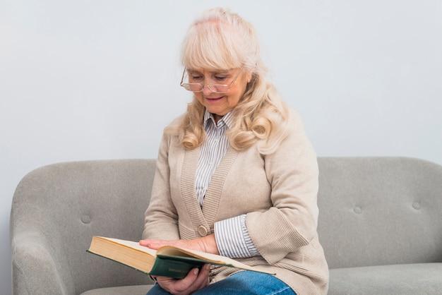 Souriant blonde femme senior assise sur un canapé en lisant un livre