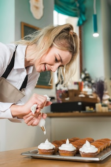 Souriant boulanger femme blonde décorant des petits gâteaux à la crème