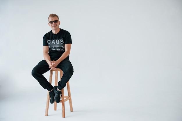 Souriant à la caméra. homme positif dans des vêtements décontractés s'amuser dans le studio contre le mur blanc