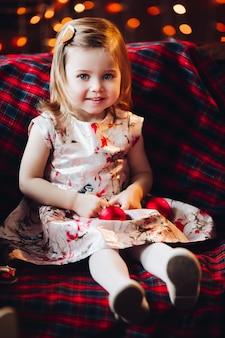 Souriant charmant bébé fille en jolie robe assis sur un banc