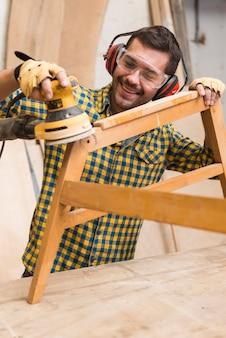 Souriant charpentier ramollissant les bords d'un meuble en bois avec ponceuse