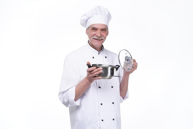 Souriant chef masculin mature avec bol en métal dans les mains sur mur blanc